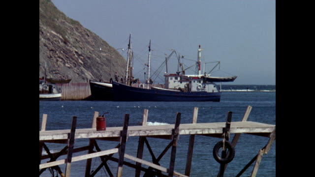 fishing boat, perce rock beyond, wooden quay in foreground - atlantic ocean stock videos & royalty-free footage