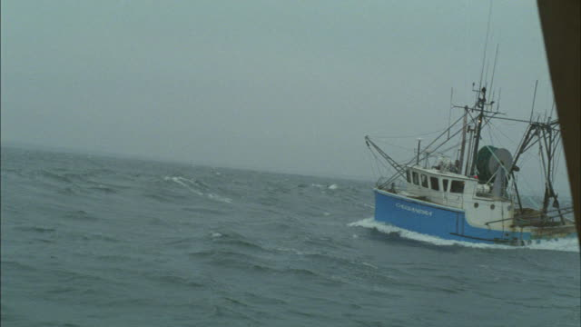 A fishing boat rocks violently in a choppy ocean.