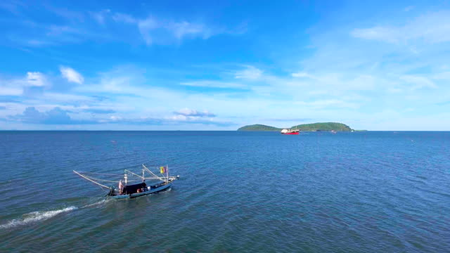 fishing boat sailing in sea with blue sky day, aerial video - rimorchiare video stock e b–roll