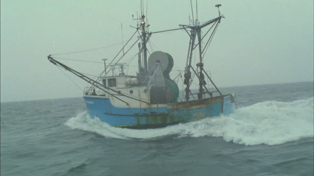 a fishing boat sails across a choppy ocean. - rough stock videos & royalty-free footage