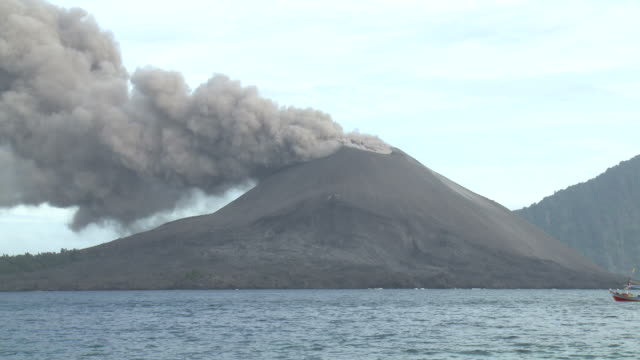 fishing boat sails close to erupting anak krakatau volcano, krakatoa, indonesia, november 2010 - indonesia volcano stock videos & royalty-free footage