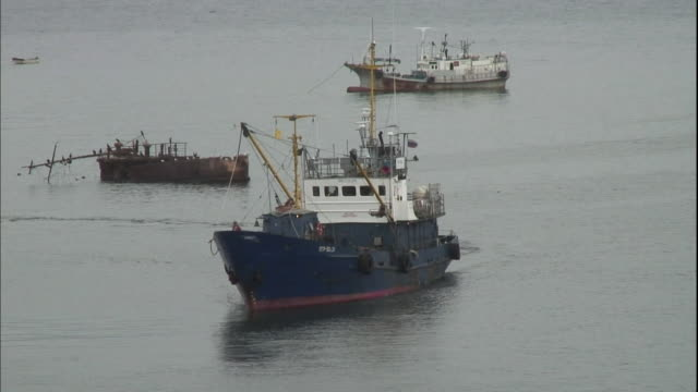 A fishing boat sails into a Kunashiri Island port.