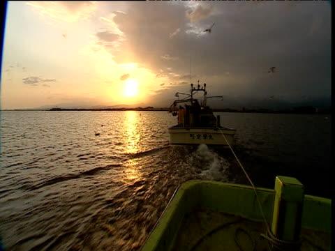 vídeos de stock e filmes b-roll de fishing boat tows smaller boat at sunset, japan - rede de pesca comercial