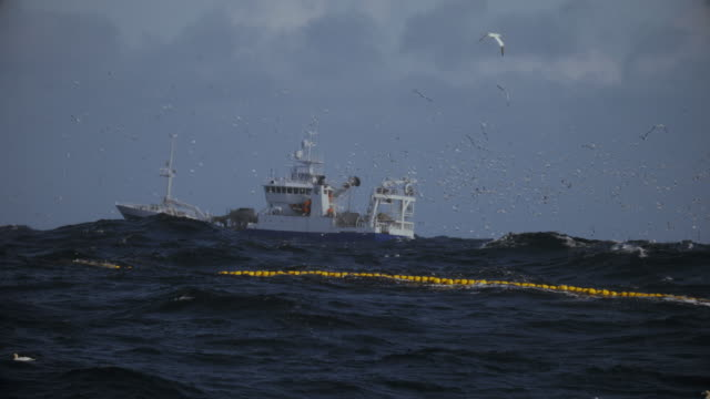 fishing boat trawler sailing a rough north sea - fishing industry stock videos & royalty-free footage