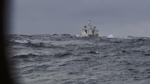fishing boat trawler sailing out at rough sea - rete da pesca commerciale video stock e b–roll