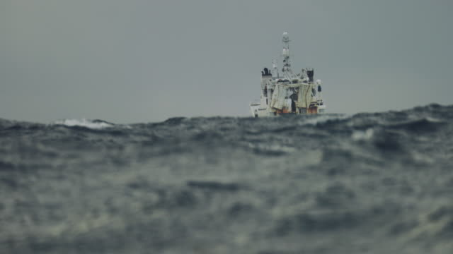 vídeos de stock e filmes b-roll de fishing boat trawler sailing out at rough sea - barco