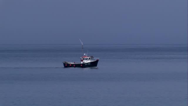 vídeos de stock, filmes e b-roll de a fishing boat trolls off the coast of crovie, scotland. available in hd. - passear sem destino