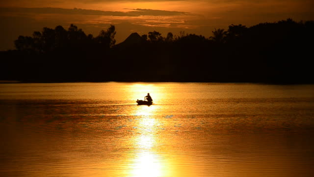 fishing boat with fisherman at sea in sunset