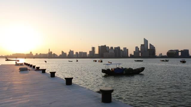 fishing boats anchored in dock against qianjiang new town (new cbd district) at sunset,hangzhou,china - エスタブリッシングショット点の映像素材/bロール