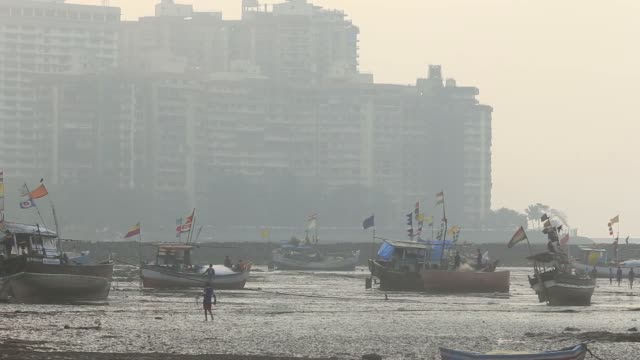 fishing boats are seen along the mahim coast in the machhimar nagar fishing village in the cuffe parade area of mumbai india on wednesday dec 4 flags... - anchored stock videos & royalty-free footage