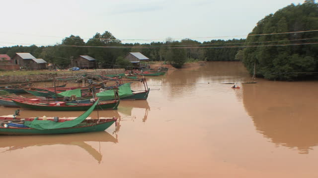 vídeos de stock e filmes b-roll de ws fishing boats docked at village on river estuary with muddy red water, sihanouksville, cambodia - aldeia de pescador