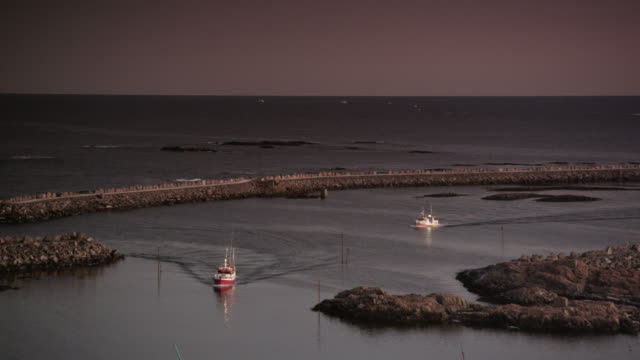 stockvideo's en b-roll-footage met fishing boats enter harbour at sunset, andenes, norway - vissersboot