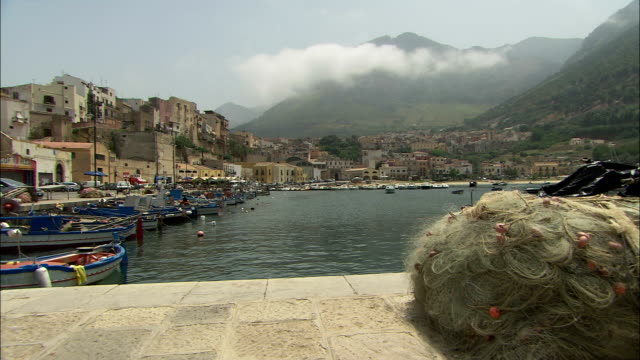 vídeos de stock e filmes b-roll de fishing boats float in the harbor of an italian port town. available in hd. - rede de pesca comercial