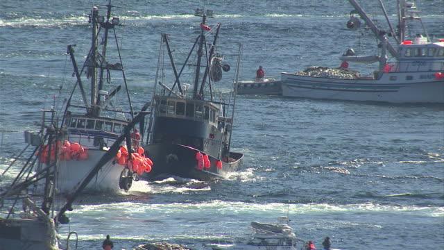 vídeos de stock e filmes b-roll de fishing boats maneuver through the harbour in sitka, alaska. available in hd. - rede de pesca comercial