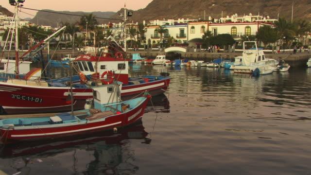 ms, fishing boats moored in harbor of puerto de mogan, gran canaria, canary islands, spain - グランカナリア点の映像素材/bロール