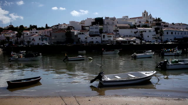 WS PAN Fishing boats moored in harbor, townscape in background / Ferragudo, Algarve, Portugal