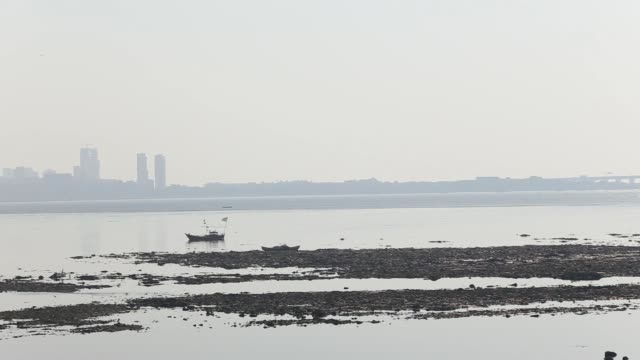 Fishing boats moored inside Mahim Creek Pan right to left from shore to pylon towers of Bandra Worli Sea Link bridge Residential and Commercial...