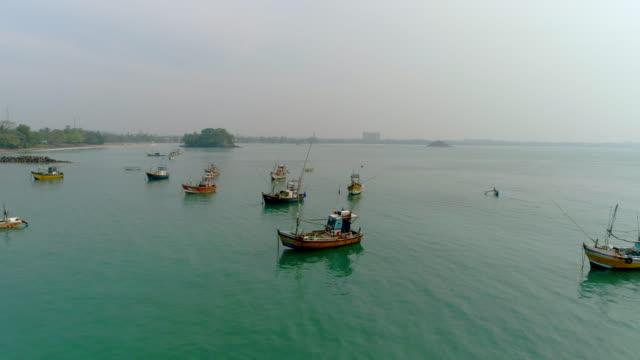 vídeos de stock, filmes e b-roll de barcos de pesca de ws atracados no oceano ensolarado, sri lanka - sri lanka