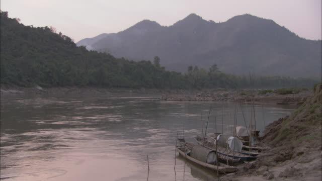 vídeos de stock e filmes b-roll de fishing boats tied up on the mekong river shore against a backdrop of cambodian mountains. - ancorado