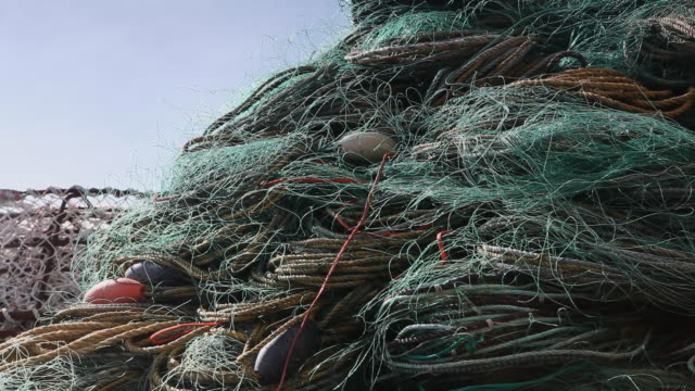 fishing nets wrapped and stacked on a dock - fischnetz stock-videos und b-roll-filmmaterial