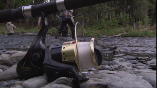 A fishing pole frames fishermen in a river in Alaska.