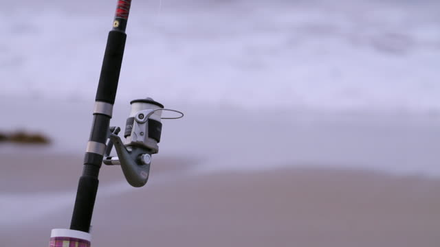 c/u fishing reel on beach - fishing rod stock videos & royalty-free footage