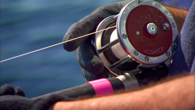 Fishing reels rods in blue black gloved hands of two unidentifiable fishermen TD CU Cast fishing line roll spinning as it unwinds stops black gloved...