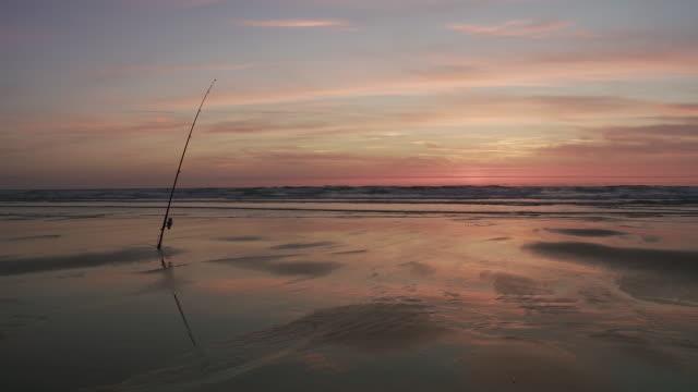 WS Fishing rod on beach in sunset / Cap de l'Homy, Aquitaine, France