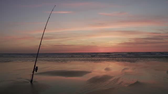 stockvideo's en b-roll-footage met ws fishing rod on beach in sunset / cap de l'homy, aquitaine, france - atlantische oceaan