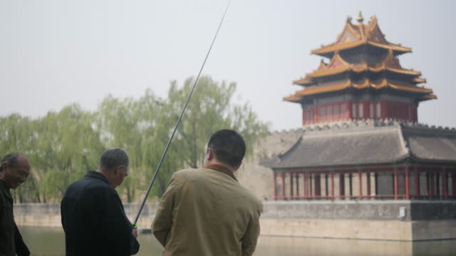 fishing the in the moat of forbidden city is no more than just killing spare time for the retirees in beijing. there are no matured fish in the moat! - 堀点の映像素材/bロール