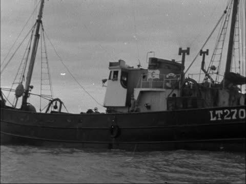 fishing trawler catches old german bomb at sea; england: off lowestoft: ext shots of trawler at sea bomb disposal squad board trawler, unda trawler... - イーストアングリア点の映像素材/bロール