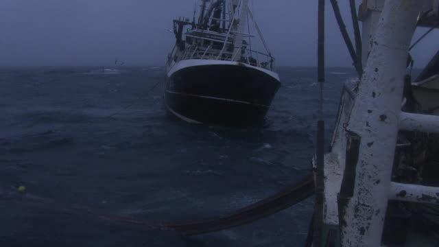 fishing trawlers haul in net on rough ocean, uk - fishing boat stock videos & royalty-free footage