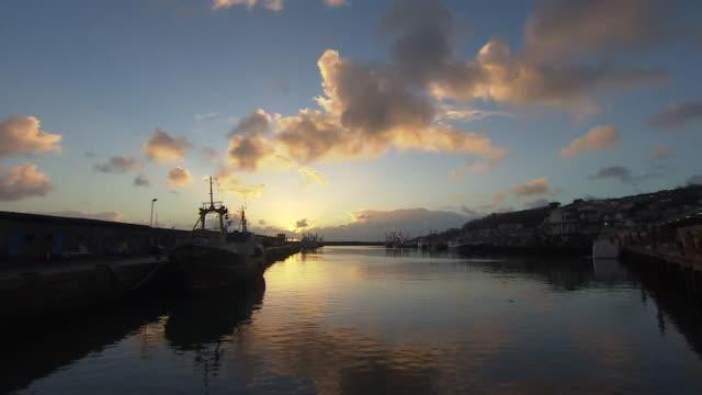 fishing trawlers moored at newlyn harbour in cornwall at dawn - ペンザンス点の映像素材/bロール