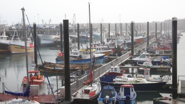 fishing vessels are seen in newlyn harbour near penzance on november 15, 2016 in cornwall, england. - ペンザンス点の映像素材/bロール