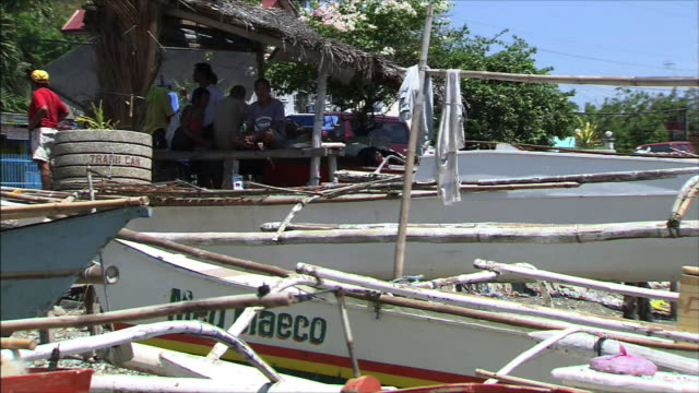 fishing village boat and a hut where men are sitting - fishing village stock videos and b-roll footage