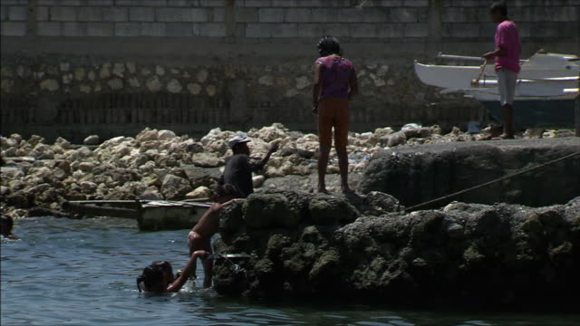 fishing village children playing on a rocky area of the beach - fishing village stock videos and b-roll footage