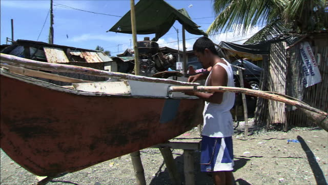 fishing village man caring for his boat - fishing village stock videos and b-roll footage