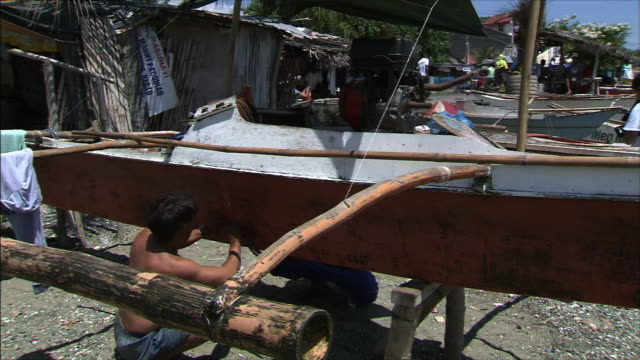 fishing village man taking care of his boat - fishing village stock videos and b-roll footage
