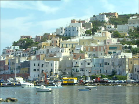 Fishing village on hillside harbour and boats in foreground Italy