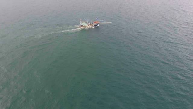 fishing-trawler boat in ocean with drone. fly approach shot. - towing stock videos and b-roll footage