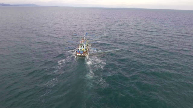 vídeos de stock e filmes b-roll de fishing-trawler boat in ocean with drone. fly approach shot. - indústria pesqueira
