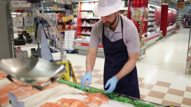 fishmonger in store arranging fish counter - protective glove stock videos & royalty-free footage