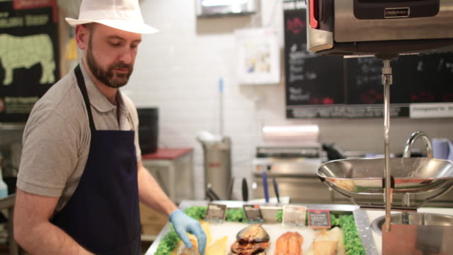fishmonger in store arranging fish counter - retail occupation stock videos & royalty-free footage