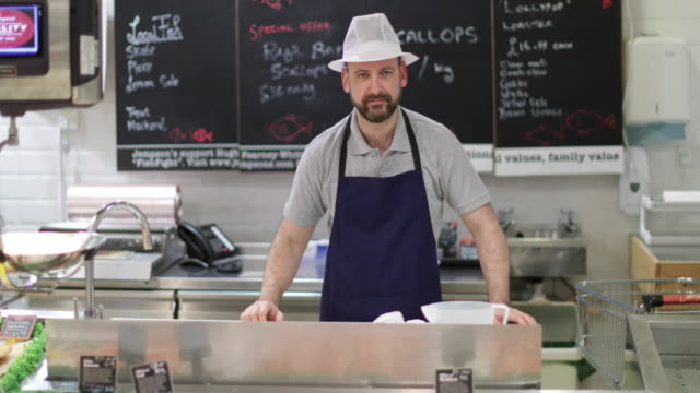 fishmonger in store looking to camera - retail occupation stock videos & royalty-free footage
