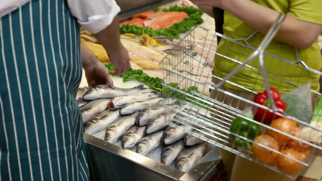fishmonger talking to female customer - shopping basket stock videos and b-roll footage