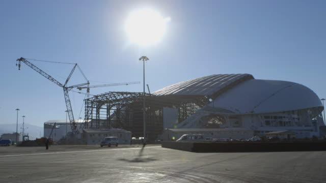 vídeos y material grabado en eventos de stock de ws fisht olympic stadium under construction tall cranes vehicles driving whitehot sun in blue sky blacktop pavement fg - sochi