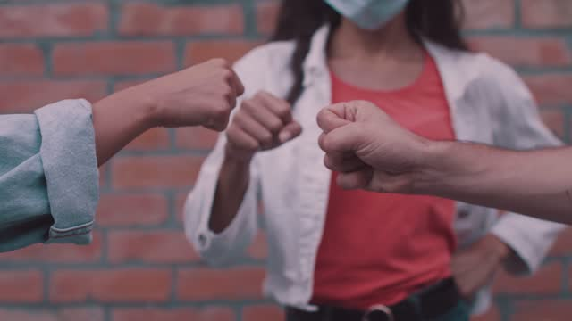 fist bumps as a new way to greet friends - three people stock videos & royalty-free footage