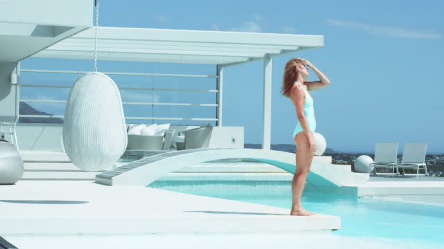stockvideo's en b-roll-footage met fit, active woman in turquoise swimsuit walks towards luxury pool and plays with shiny blonde hair - eendelig zwempak