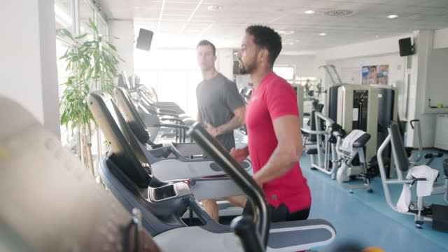 fit and focused mid adult men using treadmills at gym - mid adult men stock videos & royalty-free footage