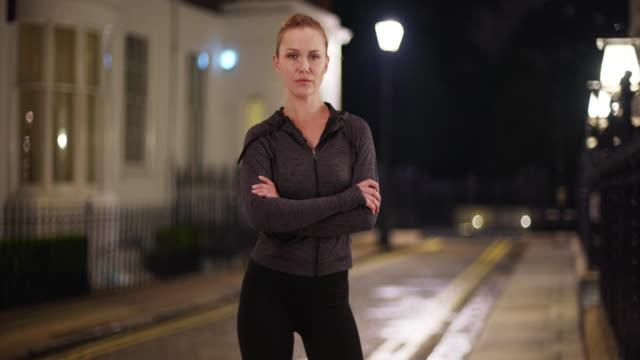 fit blonde woman trainer posing sternly with arms crossed outdoors at night - endast unga kvinnor bildbanksvideor och videomaterial från bakom kulisserna